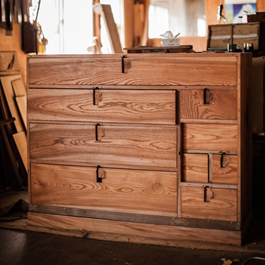 Next, the old lacquer is stripped from the tansu, revealing its original wooden exterior.